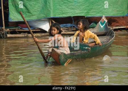 Cambodian girls in a small boat, Floating village on the Tonle Sap lake near Siem Reap, Cambodia - Stock Photo