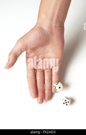 Hand throwing two dices on a white table - Stock Photo