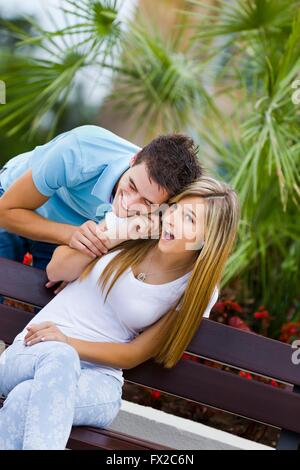 Teen couple girl and boy listen to cellphone call talk together nosy curiosity curious mobile phone attractive fun - Stock Photo