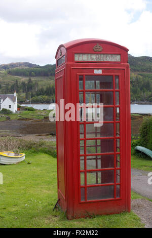Red telephone box in Plockton, in Ross and Cromarty, in the Highlands of Scotland - Stock Photo
