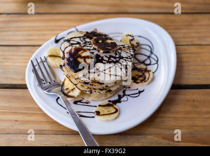 Stack of Pancakes in a restaurant with banana and chocolate sauce on top. - Stock Photo