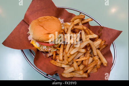 Cheeseburger with fries in a metal basket - Stock Photo