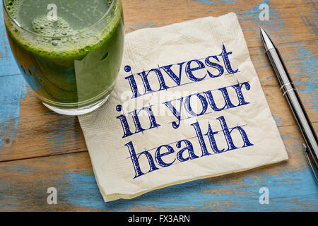 invest in your health advice or reminder - handwriting on a napkin with a glass of fresh, green, vegetable juice - Stock Photo