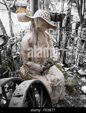 An old crumbling but beautiful statue of a woman with flowers and a cheetah print brimmed hat in a weedy garden, - Stock Photo