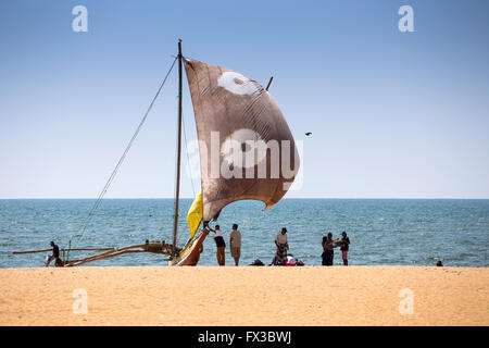 View of Traditional Outrigger Fishing Boat (Oruva) with Sail on Negombo Beach, Sri Lanka - Stock Photo