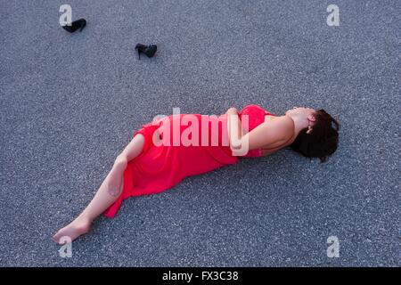 Lying on road detached shoes in long Red dress young woman - Stock Photo