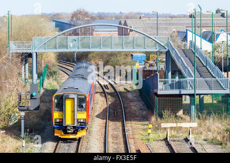 Footbridge over a railway line with an East Midlands Trains Diesel Multiple Unit (DMU) train travelling under the - Stock Photo