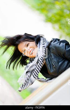 Young woman and very strong wind messy hair laughing happy bending over scarf Black jacket outdoors attractive - Stock Photo