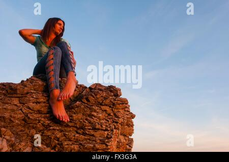 Young woman is watching sunset rock barefeet against sky free copy space above single seated sitting atop big rock - Stock Photo