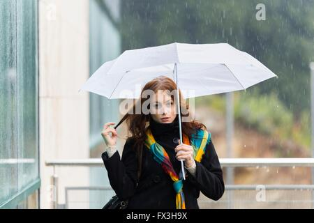 Teenager girl rainy day White umbrella facing camera eyescontact pull pulling hair rain street streetlife colorful - Stock Photo
