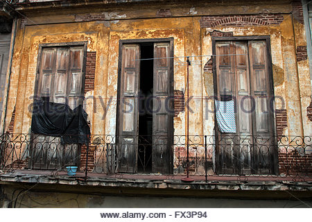 Tall doors holes patched up with makeshift material wrought iron balcony across from & Tall doors patched up with makeshift material wrought iron Stock ...