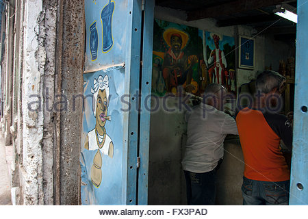 Men in store selling Cuban Religious Articles and Pottery, painting of cigar smoking Santeria woman on door, - Stock Photo