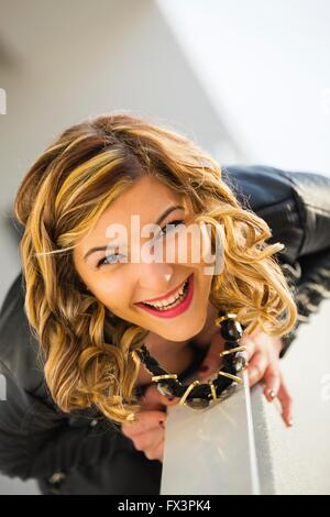 Teen-girl portrait curly-hair laughing outdoors prone position body head responsive response smile smiling attractive - Stock Photo