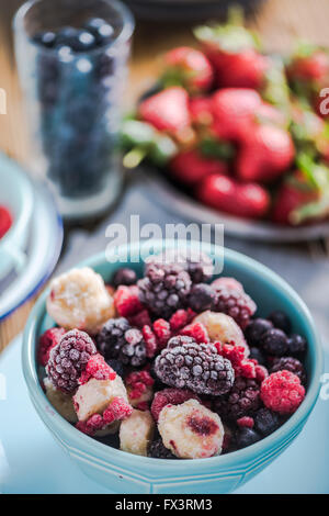 Frozen berry fruits, smoothie ingredients. In vibrant blue bowl, on wooden table - Stock Photo