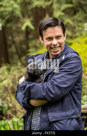 Mand holding Fitzgerald, a 10 week old black Pug puppy in Issaquah, Washington, USA - Stock Photo