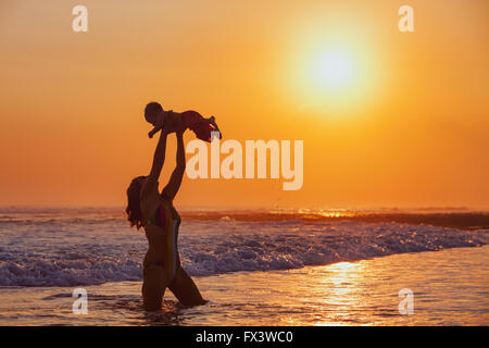 Happy family swimming fun on sea beach - mother tossing up baby son into mid air, catching on sunset sky on sun - Stock Photo