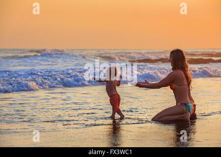 Family swimming fun in sea beach surf Happy mother, baby son first step - toddler run to ocean wave on sunset sky - Stock Photo