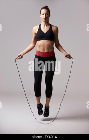 Athletic blonde woman skipping rope, full length shot - Stock Photo