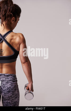 Muscular dark haired young woman using dumbbells, back view - Stock Photo