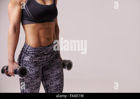 Dark haired young woman using dumbbells, mid section crop - Stock Photo