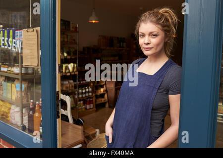 Portrait Of Female Delicatessen Owner Standing In Shop Door - Stock Photo