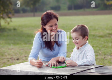 Young woman teacher teaches little young boy in white shirt painting with the brush to make artisanal pasta beads - Stock Photo