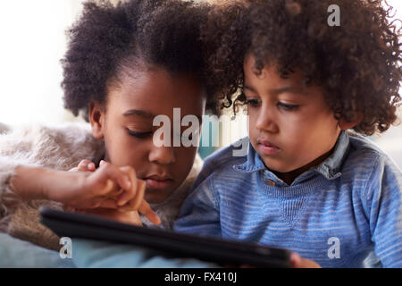 Brother And Sister Using Digital Tablet At Home Together - Stock Photo