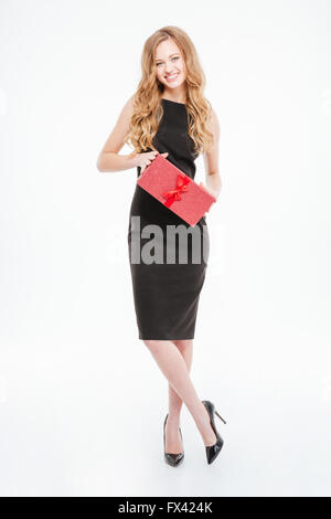 Happy beautiful young woman in black dress and high heels shoes standing and holding a gift over white background - Stock Photo