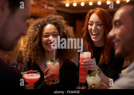 Group Of Friends Meeting For Evening Drinks In Cocktail Bar