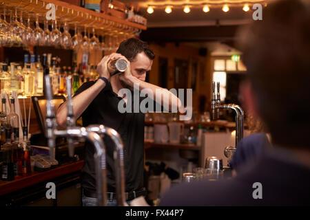 Barman Making Cocktail In Bar Using Shaker - Stock Photo