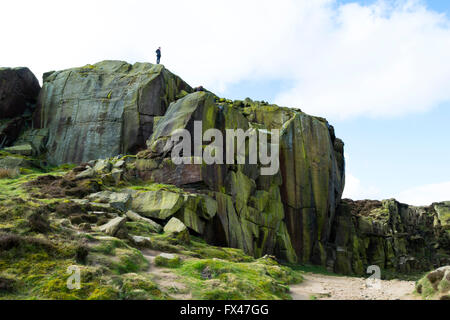 Person standing on top of climbing rocks near the Cow and Calf within an old quarry at Ilkley Moor, West Yorkshire, - Stock Photo