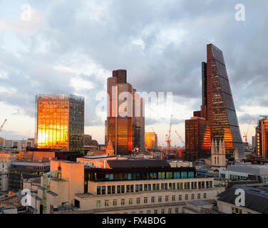 Stock Exchange Tower, Tower 42 and the Cheesegrater reflecting the evening setting sun in the City of London financial - Stock Photo