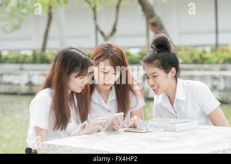 Portrait of group of students having fun with smartphones after class. - Stock Photo