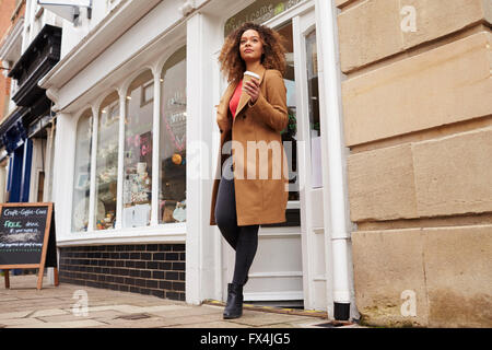 Female Customer Coming Out Of Cafe With Takeaway Coffee - Stock Photo