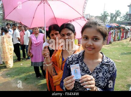 A young woman shows her voter identification as she stand in long lines to cast her vote at a remote polling station - Stock Photo