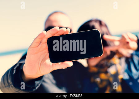 closeup of a young man and a young woman taking a self-portrait with a smartphone while she is doing the victory - Stock Photo