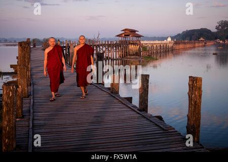 Two monks walk at sunrise across the wooden U Bein's Bridge near Amapura in Mandalay. - Stock Photo