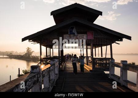 Two school girls walk across U Bein's Bridge near Amapura in Mandalay at sunrise - Stock Photo