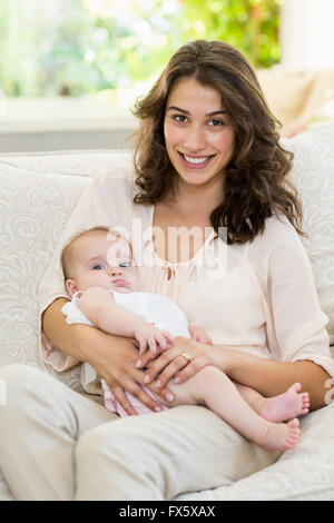 Mother holding her baby on lap in living room - Stock Photo