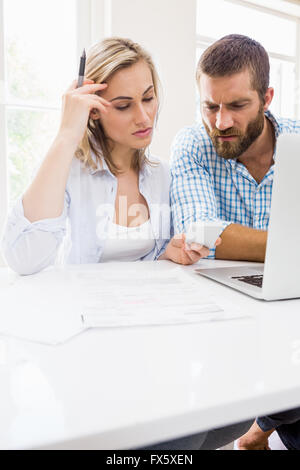 Worried couple looking at mobile phone - Stock Photo