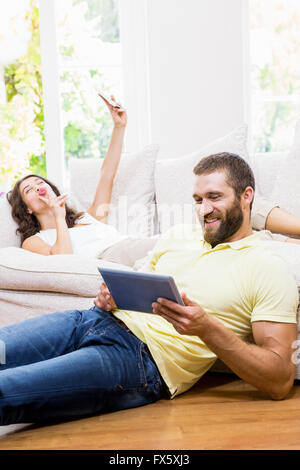 Man using digital tablet while woman taking selfie from mobile phone - Stock Photo