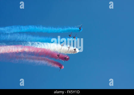 Red Arrows aerobatic team formation flying against a blue sky - Stock Photo