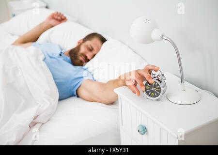 Sleeping man awakened by a alarm on bed - Stock Photo
