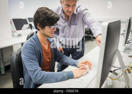 Computer teacher assisting a student - Stock Photo