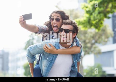 Man giving piggyback to woman - Stock Photo