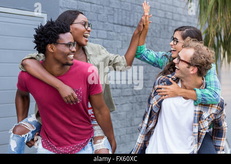 Young men giving piggyback to women - Stock Photo