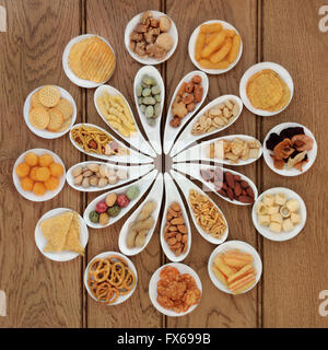 Savory snack food selection in porcelain dishes over oak background. - Stock Photo