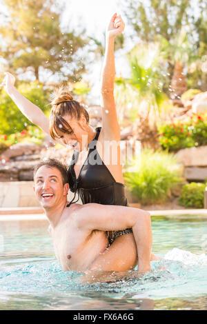 Caucasian man carrying girlfriend piggyback in swimming pool - Stock Photo