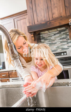 Caucasian mother and daughter washing hands in kitchen sink - Stock Photo