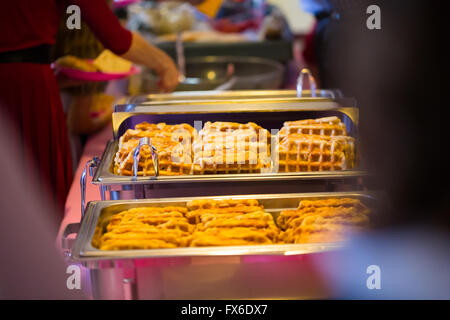 Buffet dinner at this wedding reception includes breakfast waffles among other interesting and unique food choices. - Stock Photo